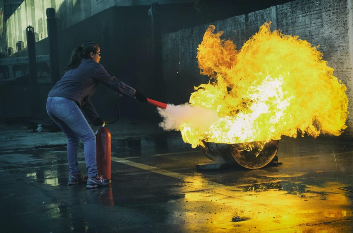 adult using fire extinguisher on fire